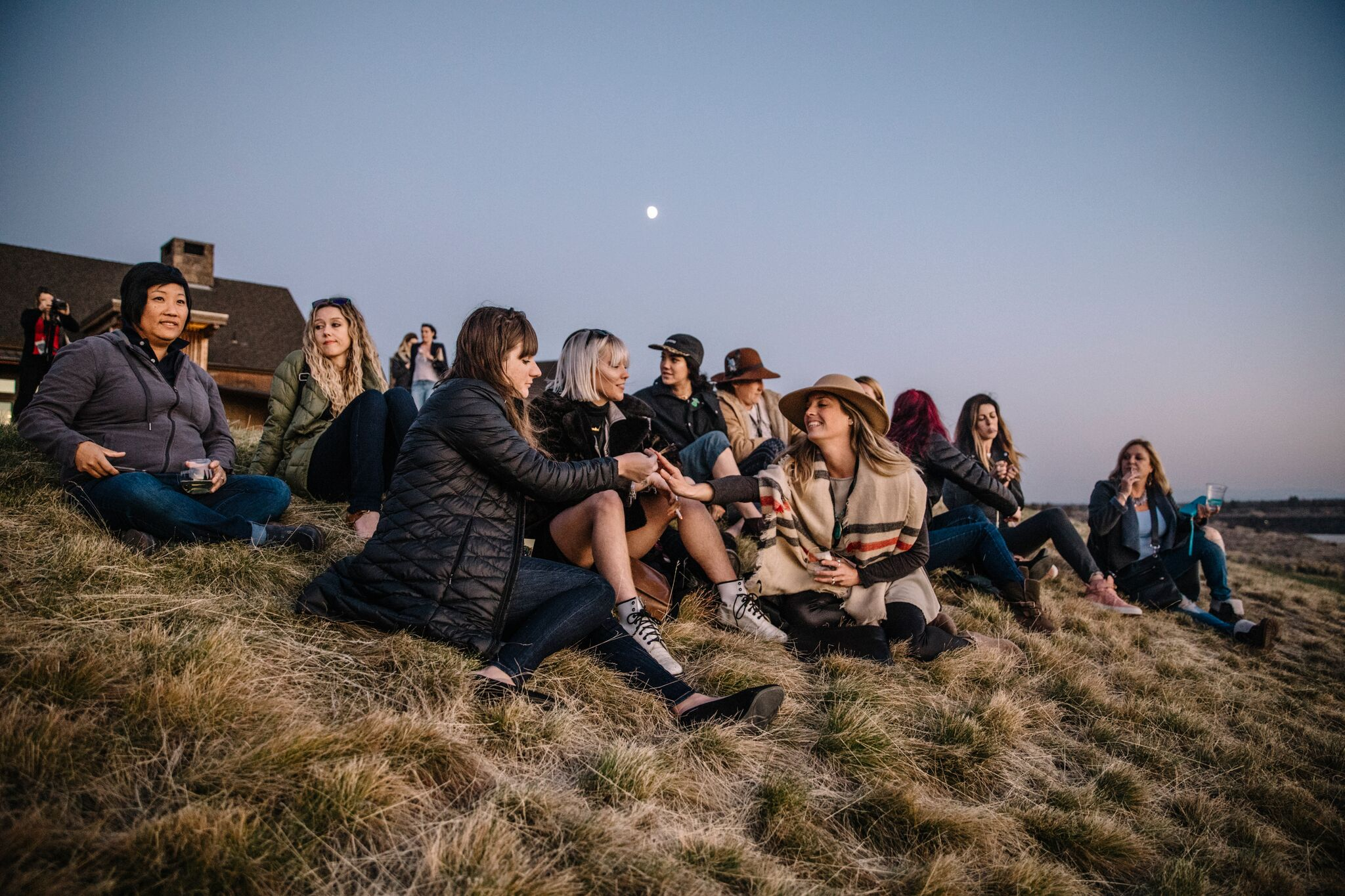 Women gather on grassy hill to watch sunset and share cannabis at the Hustle Hard Retreat in Bend, Oregon.