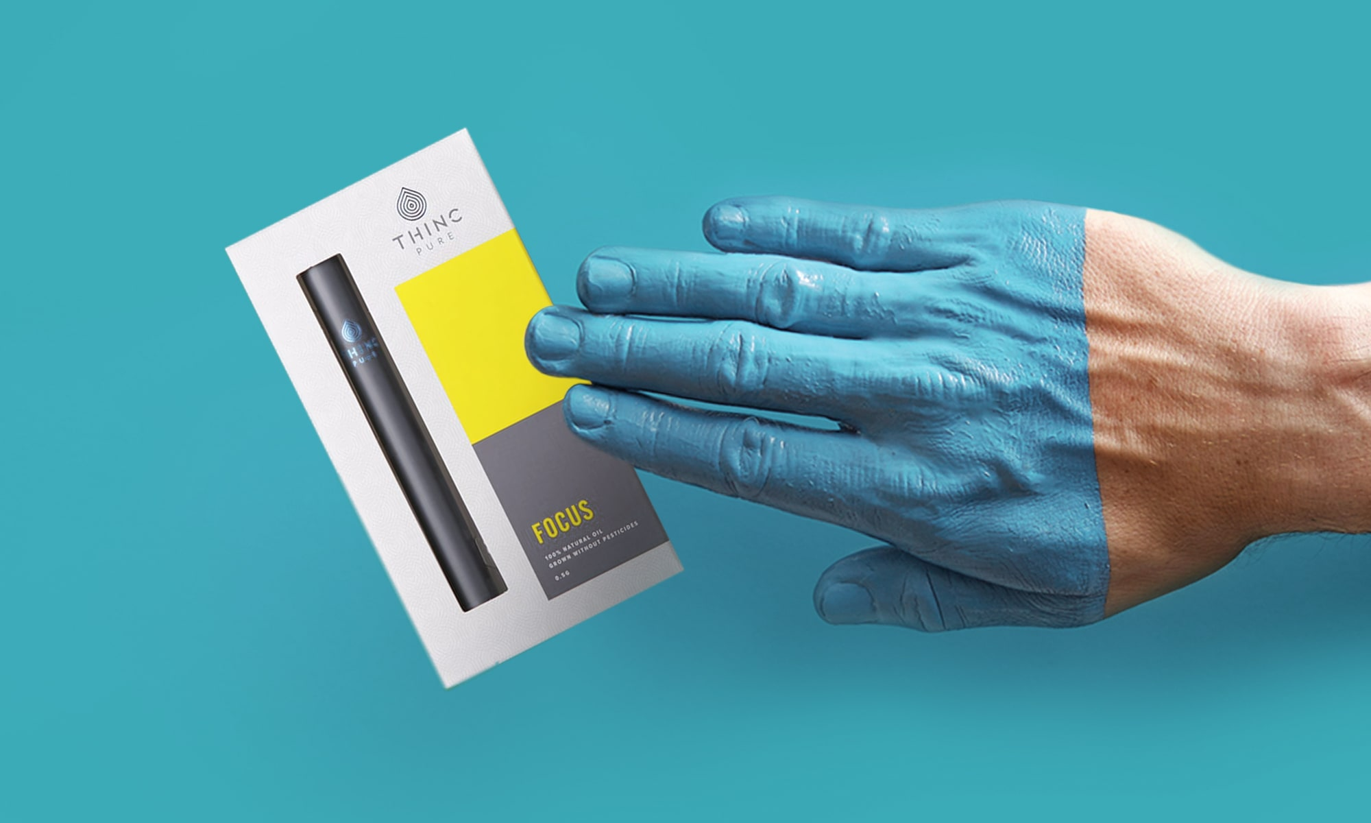 Half blue-painted hand next to yellow Thinc Pure Focus cannabis box on bright blue background.