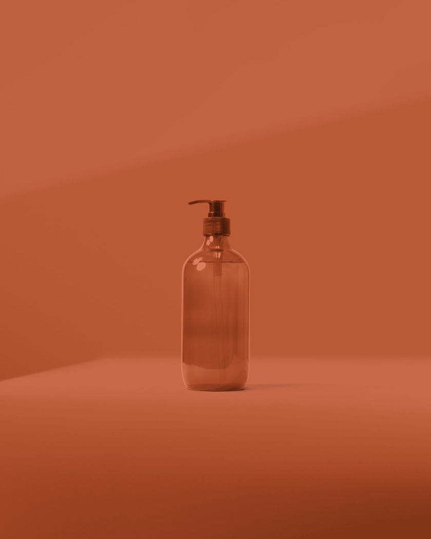 Dark orange monochromatic environment with glass hand pump bottle on solid flat surface.