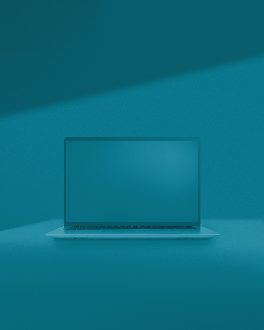 Dark teal monochromatic environment with open laptop on solid surface.